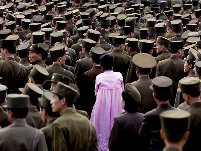Женщина стоящая в толпе солдат